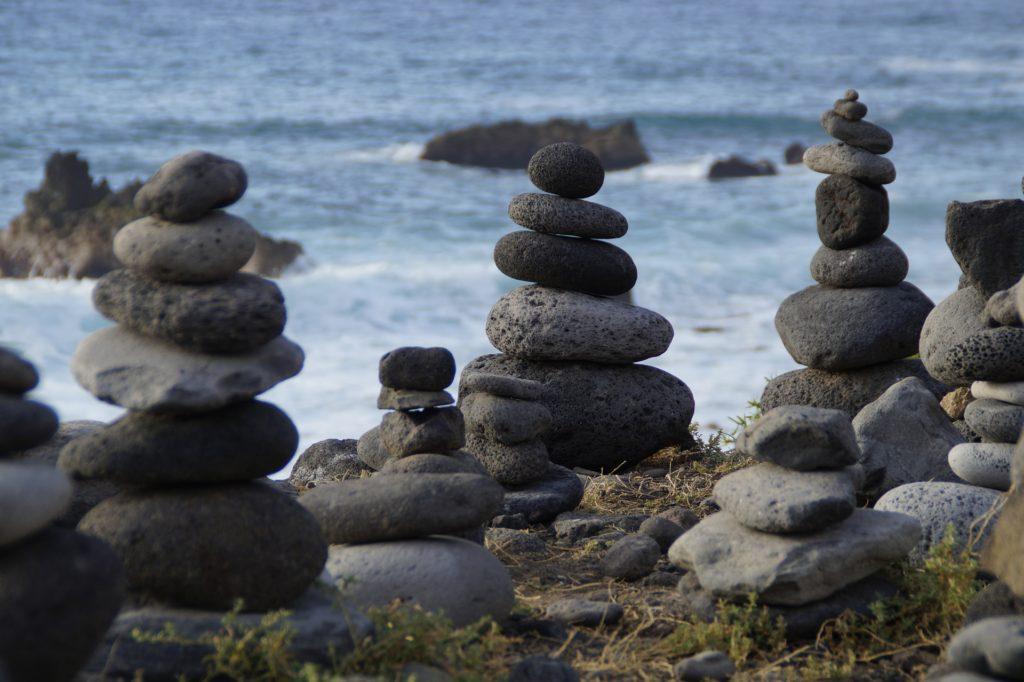 Einige Steine sind am Meer übereinander gestapelt.