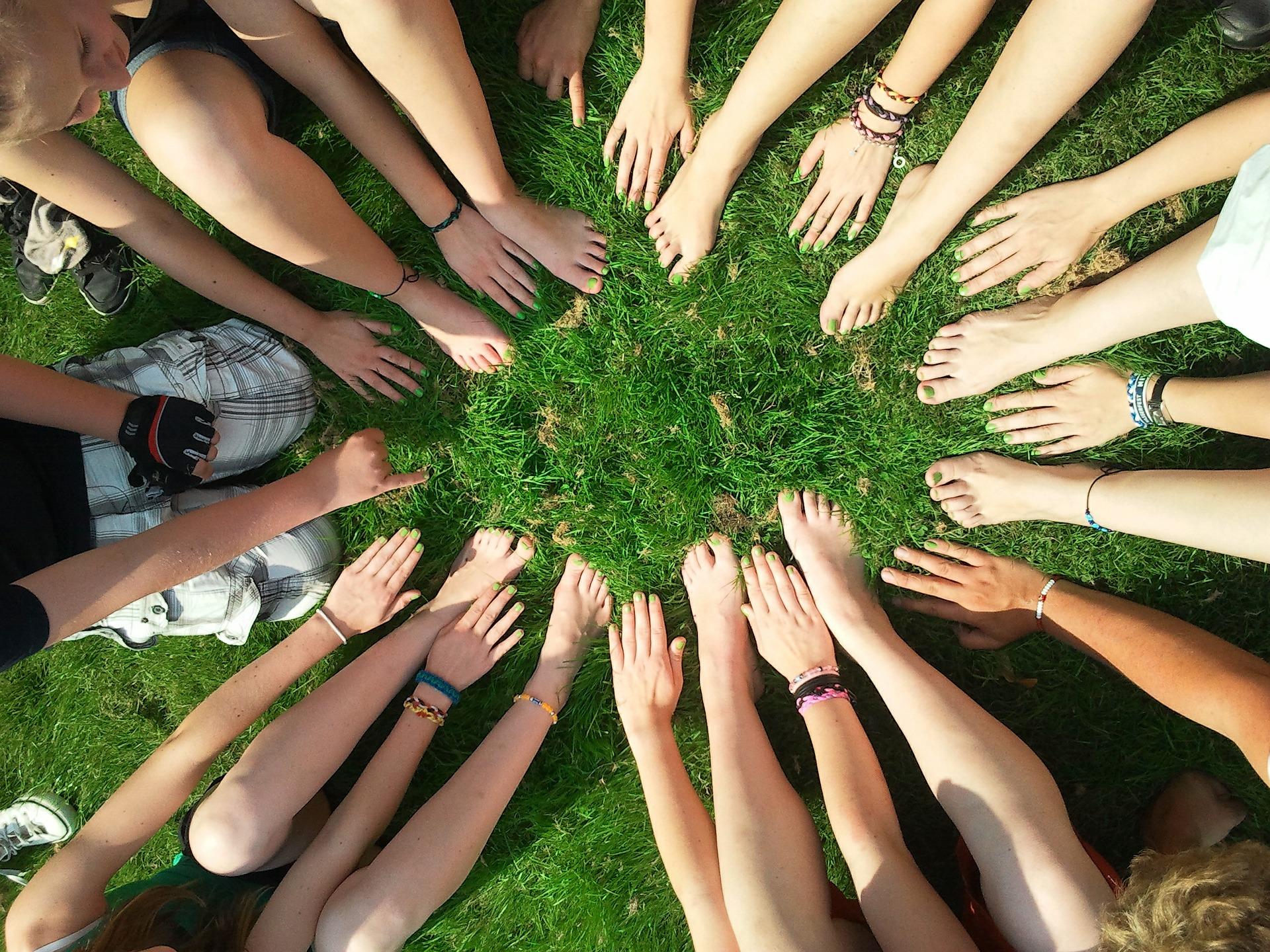 Viele verschiedene Hände und Füße formen einen Kreis.