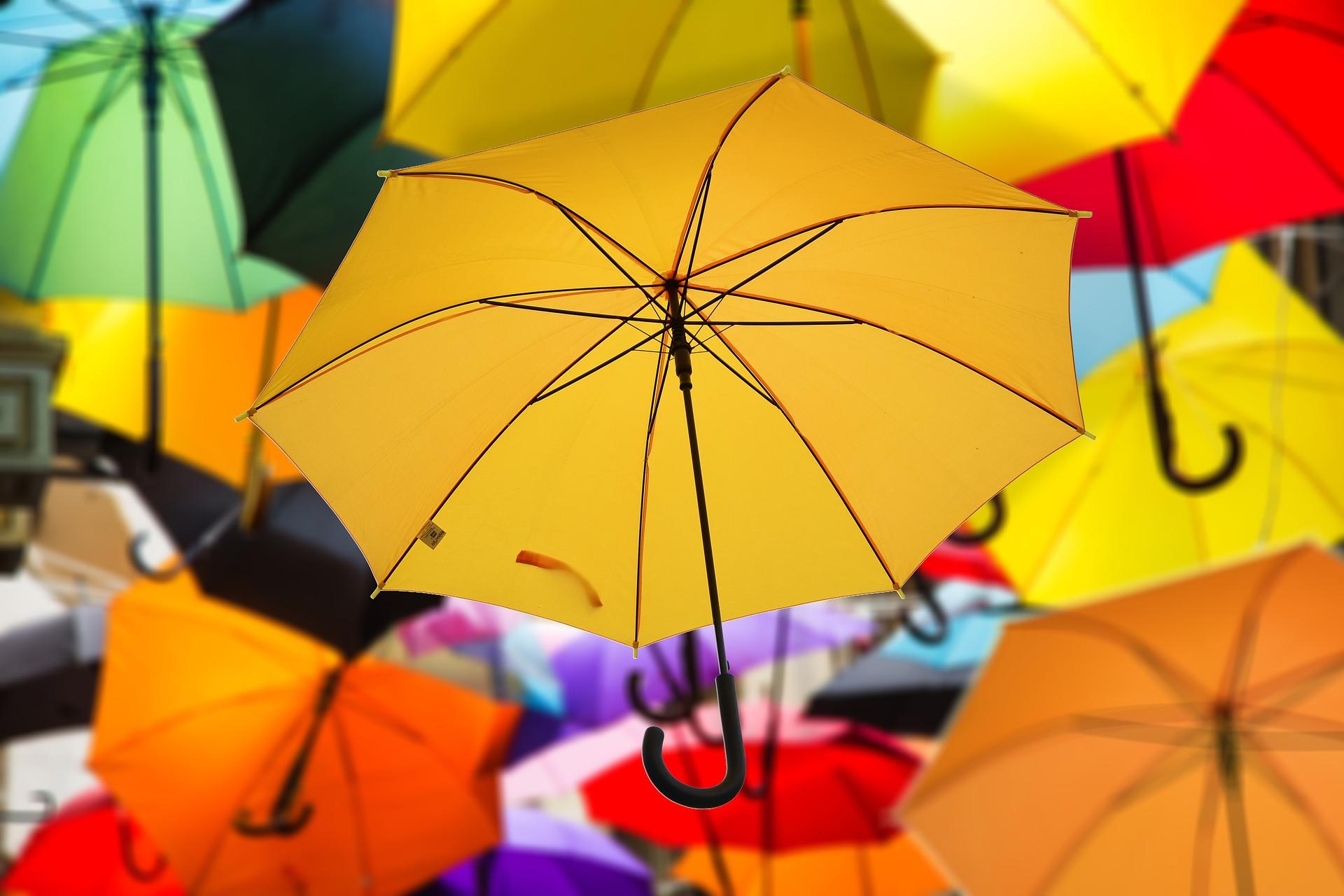 Viele bunte Regenschirme hängen übereinander.