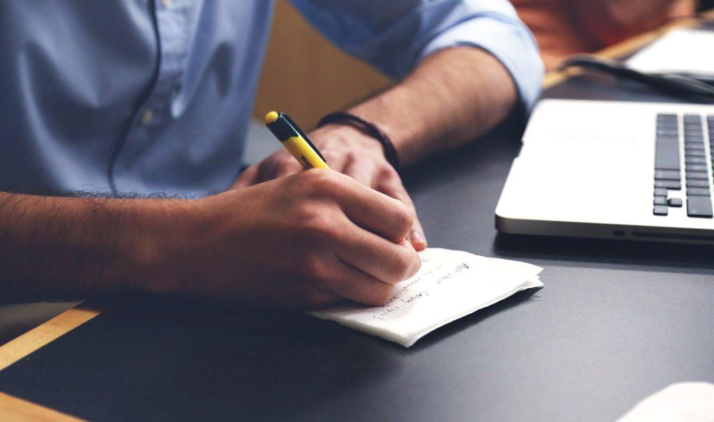 Ein Mann schreibt an seinem Arbeitsplatz.