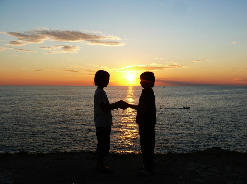 Zwei Kinder halten am Strand Händchen