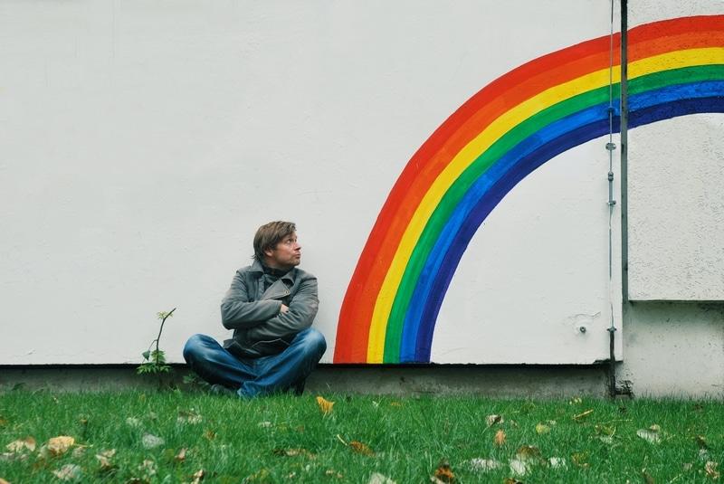 Mann sitzt neben Regenbogen