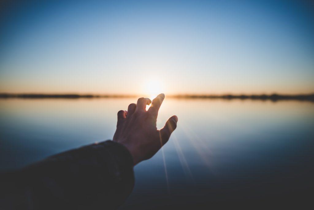 Eine Hand wird zum Licht ausgestreckt