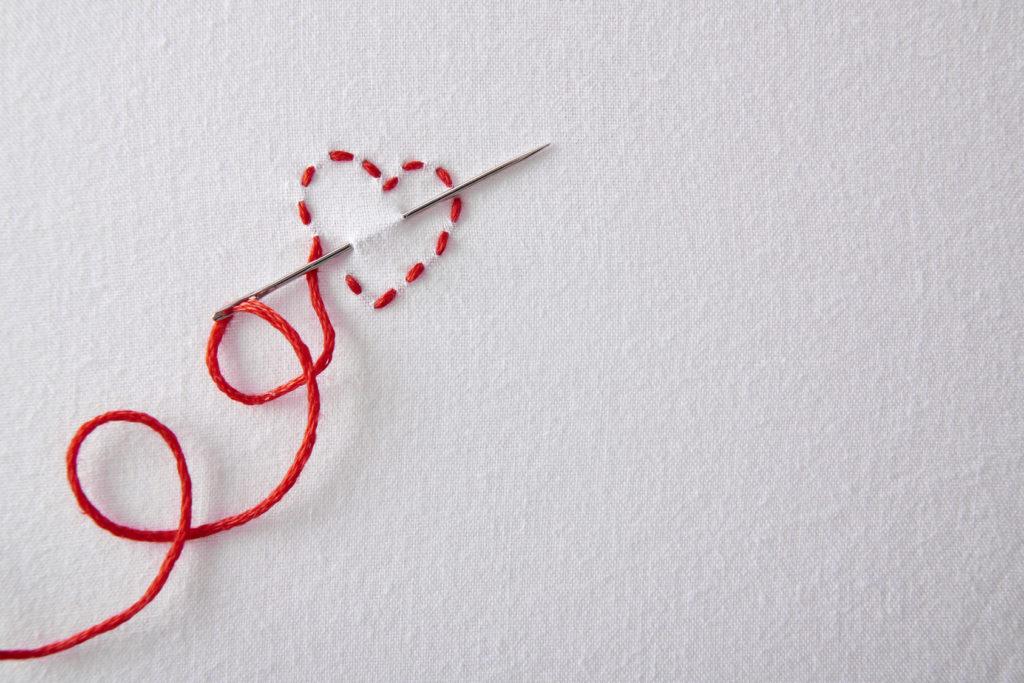 Nadel mit rotem Faden und Herz