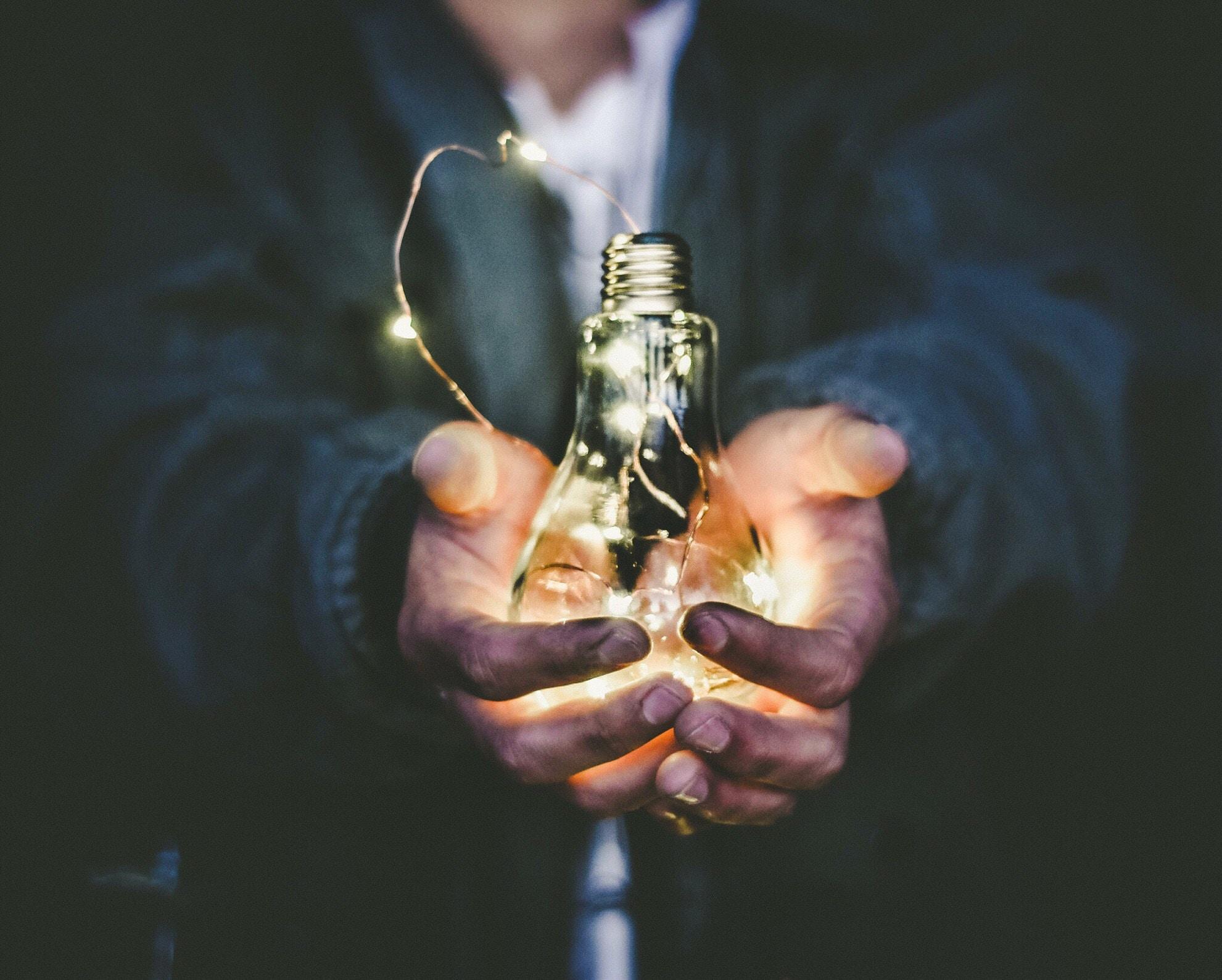Mann hält Glühbine in den Händen