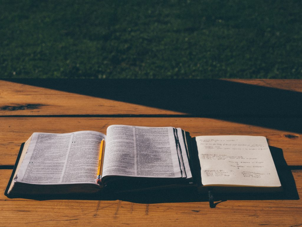 Geöffnete Bibel mit Bleistift und Notizblock