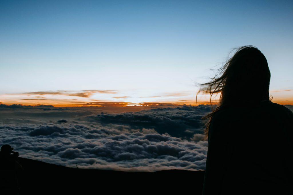 Eine Frau überblickt den Sonnenaufgang über den Wolken.