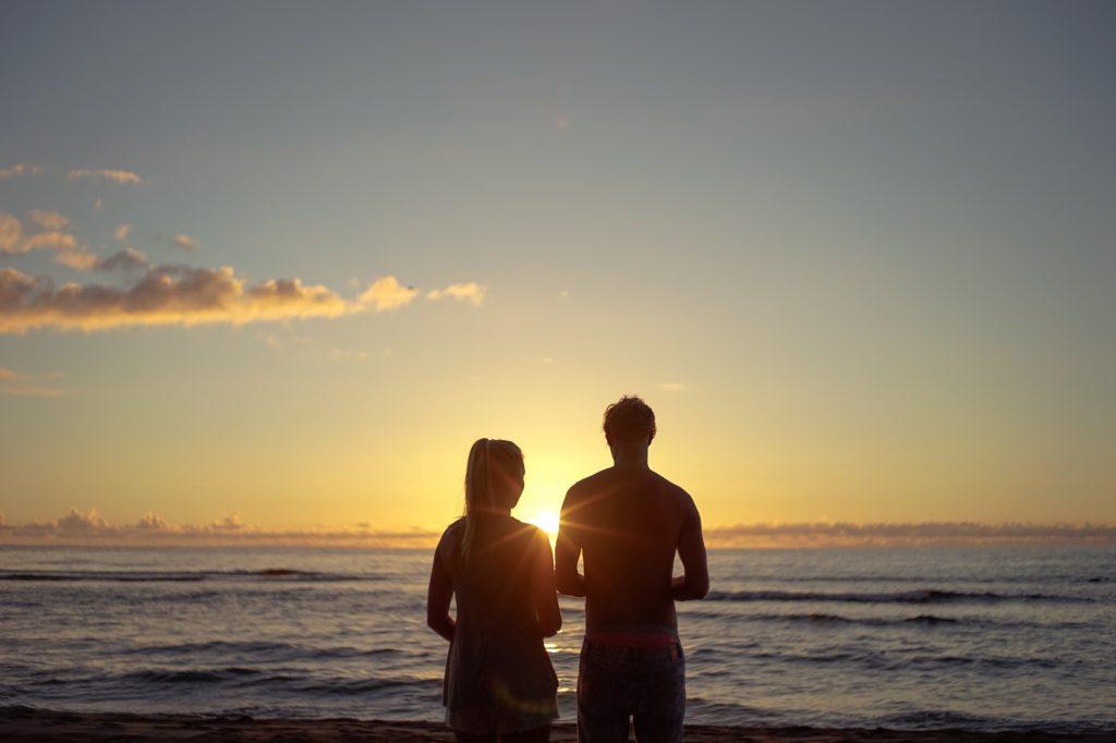 Paar blickt über das Mehr in den Sonnenaufgang.