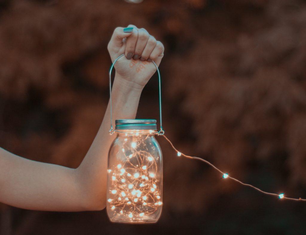 Hand hält ein Licht