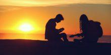 Silhouette eines Pärchens, das im Sonnenuntergang Gitarre spielt.