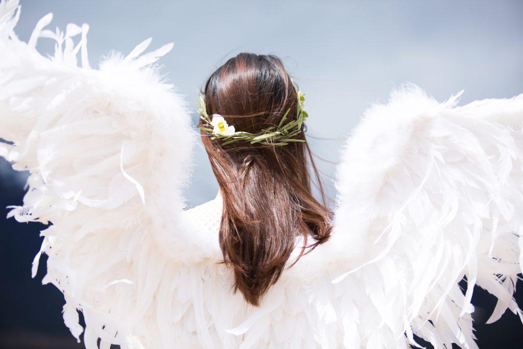 Frau mit Engelsflügeln und Blumenkranz im Haar.