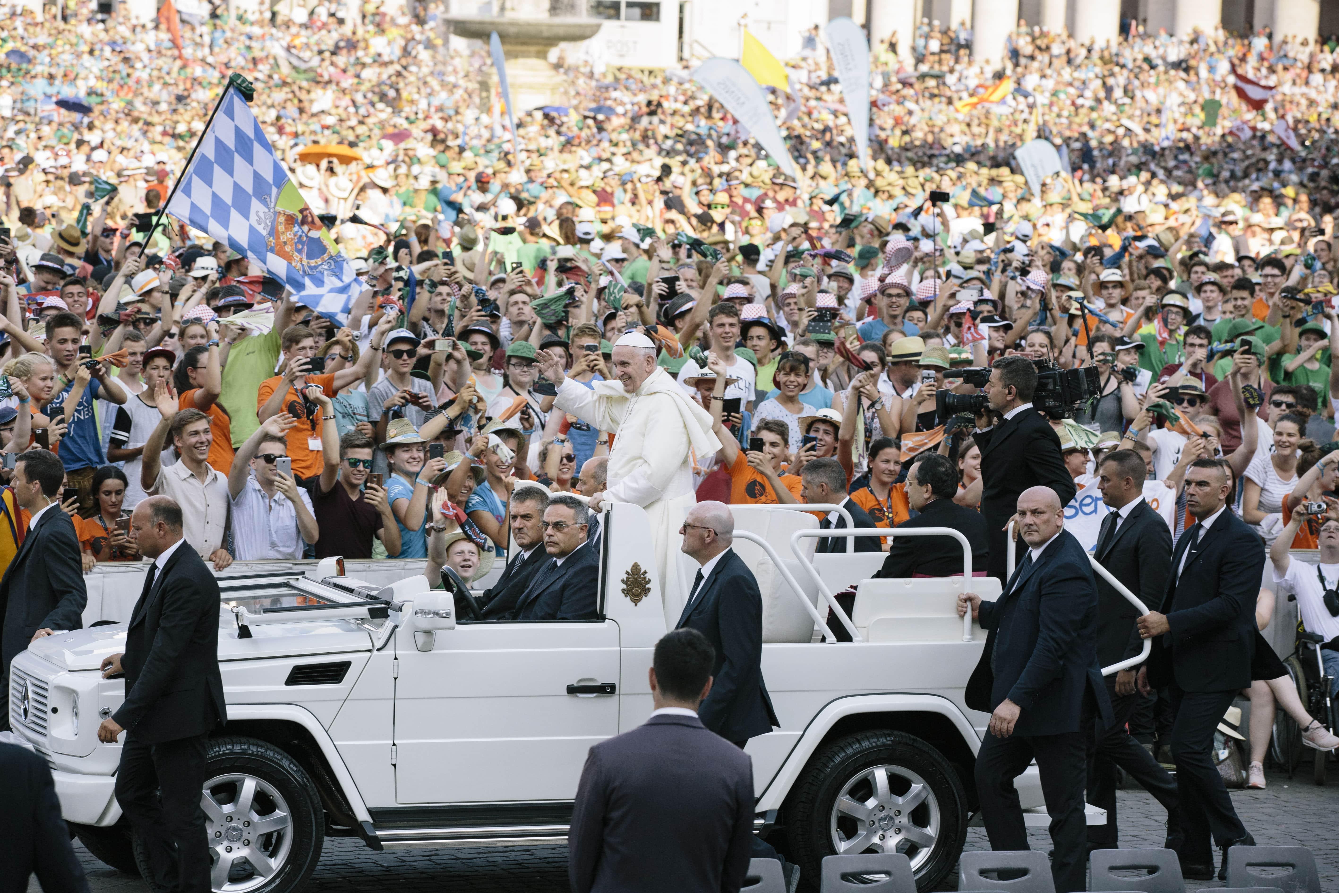 Papst Franziskus fährt mit dem Papamobil durch die Menge der Ministranten.