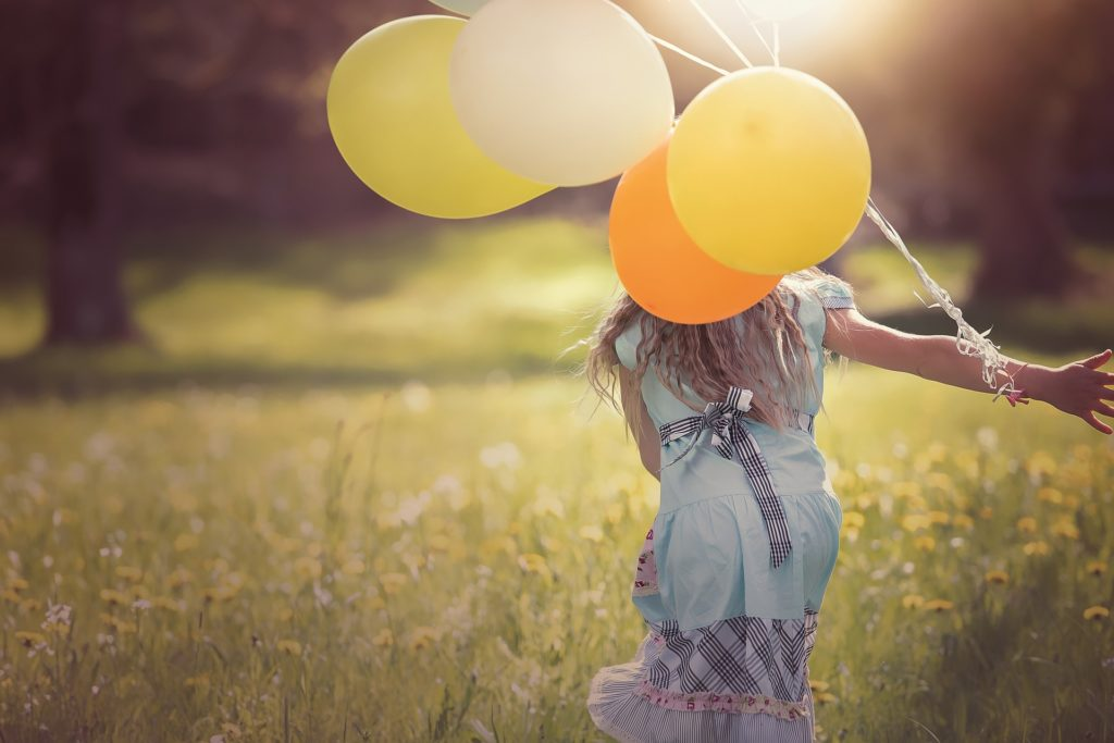 Mädchen mit Luftballon läuft über Wiese