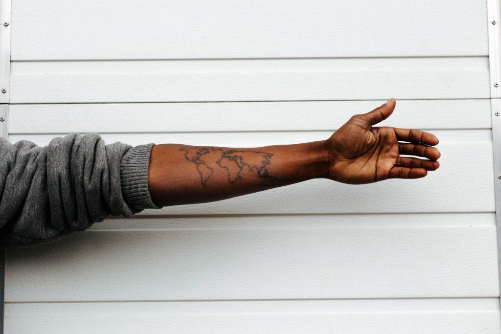 Arm mit einem Weltkarten-Tattoo
