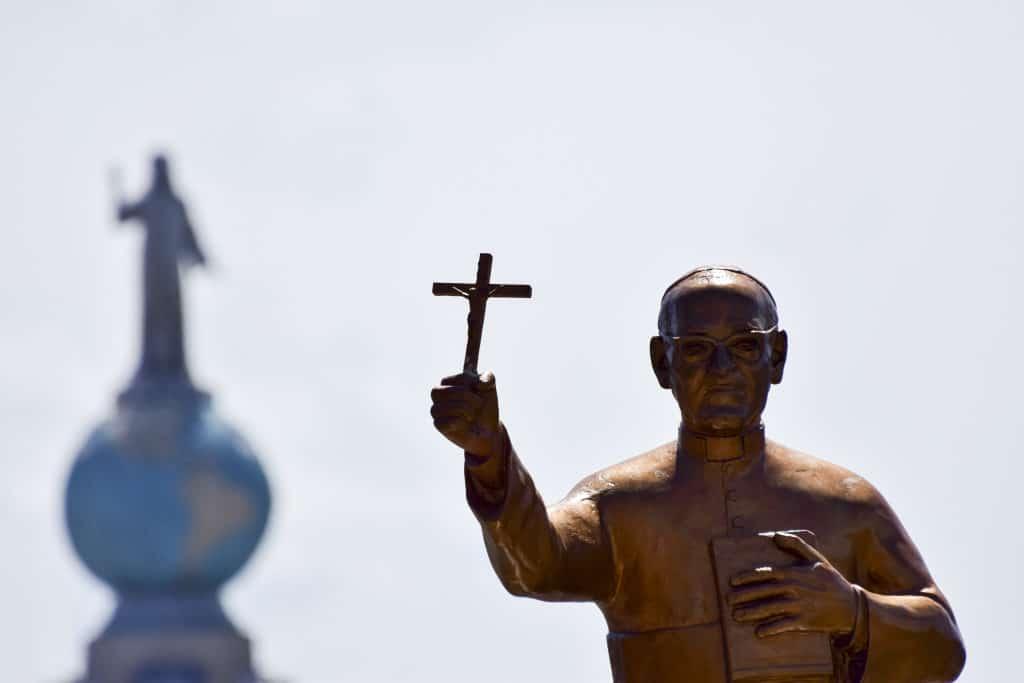 Eine Statue von Oscar Romero, der ein Kreuz hält, steht bei dessen Seligsprechung am 23. Mai 2015 in San Salvador vor dem Denkmal Monumento al Divino Salvador del Mundo, dem Wahrzeichen von El Salvador.
