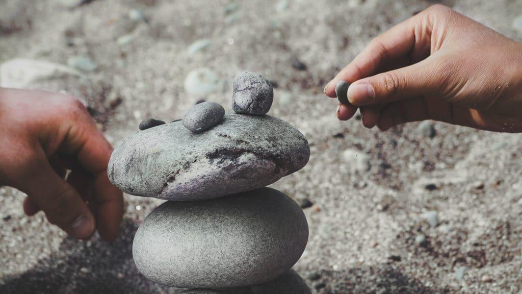 Hände bauen Trum aus Steinen