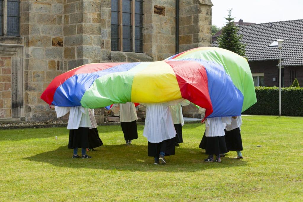Ministranten mit Schwungtuch vor einer Kirche