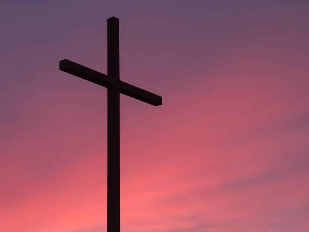 Kreuz vor rotem Himmel