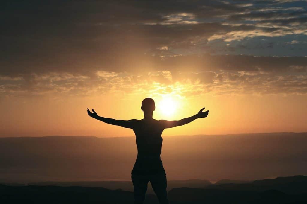 Mann mit ausgebreiteten Armen vor einem Sonnenaufgang