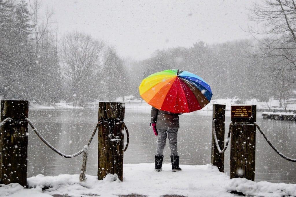 eine Person steht mit buntem Schirm im Schneetreiben