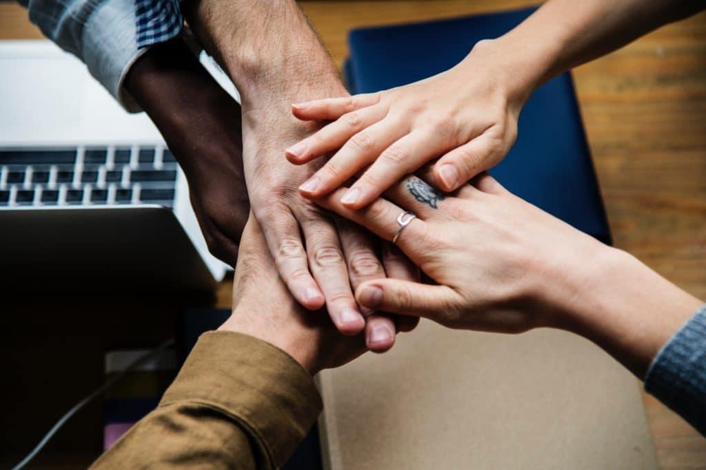 Händer verschiedenen Leute verschränken sich