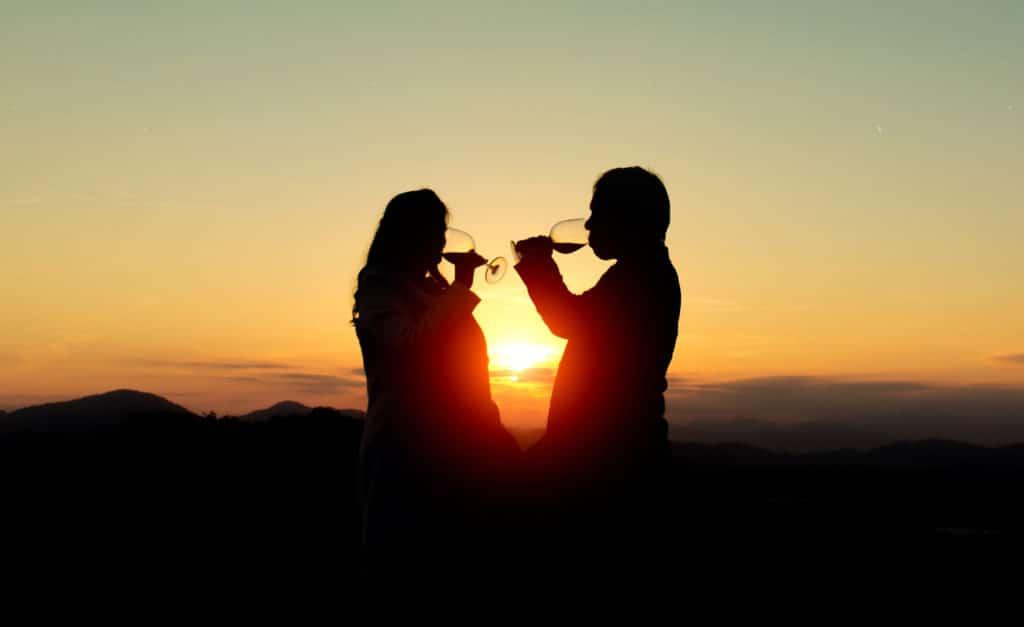 Ein Paar trinkt Wein vor einem Sonnenuntergang