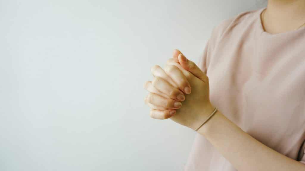 Frau hat Händ zum gebet gefaltet