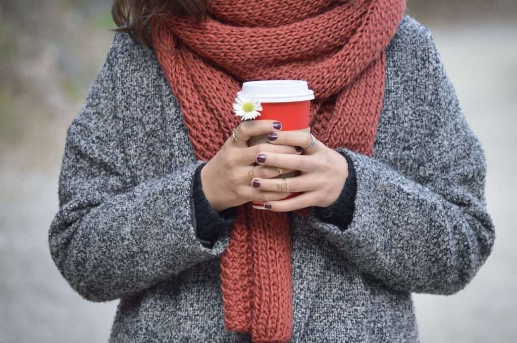 Frau hält Kaffeebecher