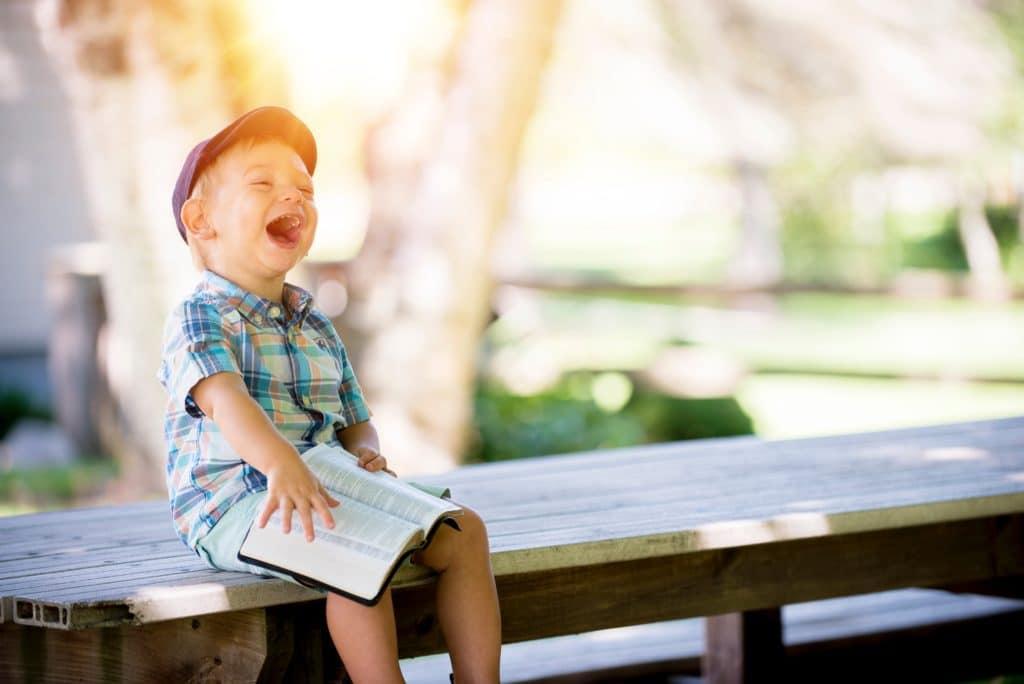 Junge sitzt mit einem Buch auf einem Steg und lacht