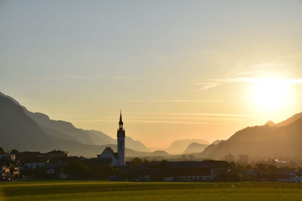 Dorf mit Bergen und Sonnenaufgang