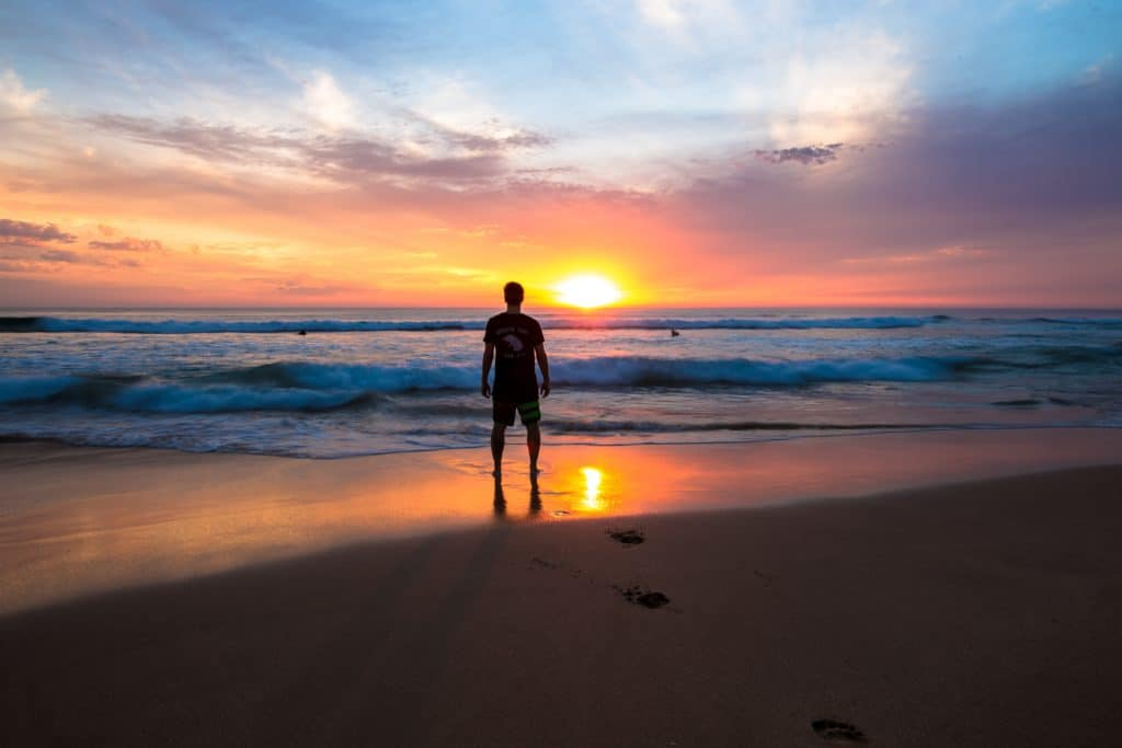 Mann steht bei Sonnenuntergang am Strand