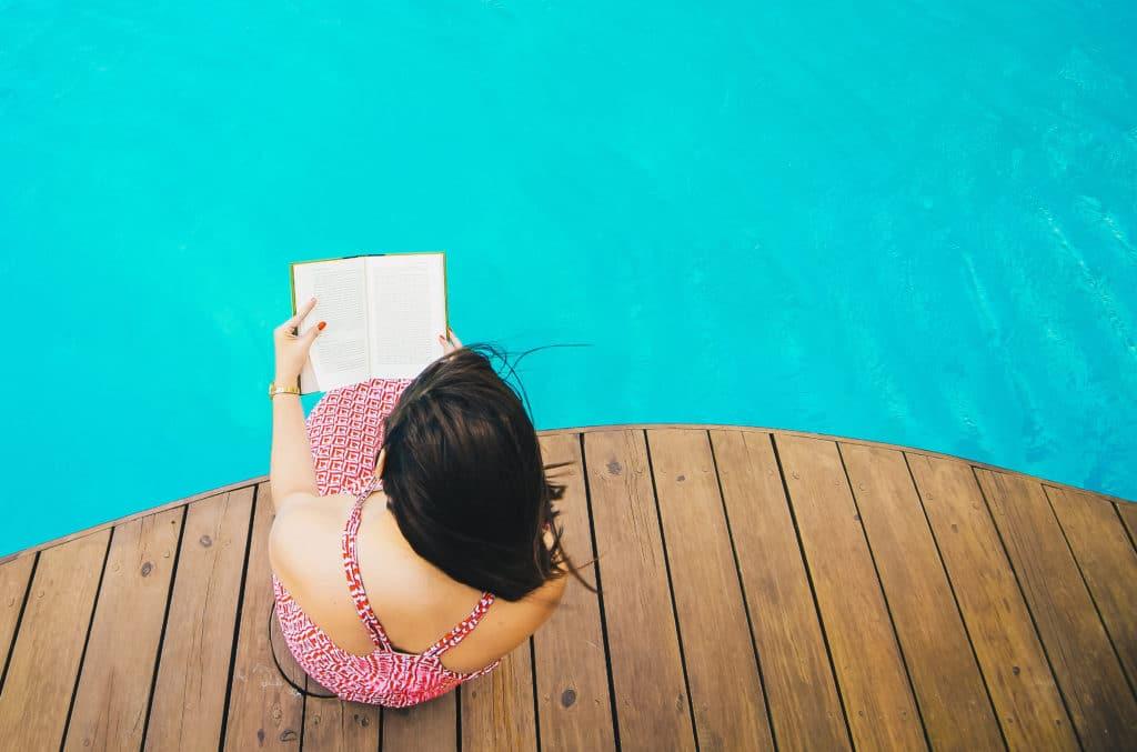 Frau liest am Swimmingpool