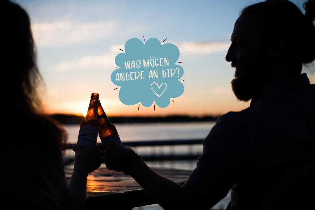 Zwei Menschen stoßen am Strand mit Bier an