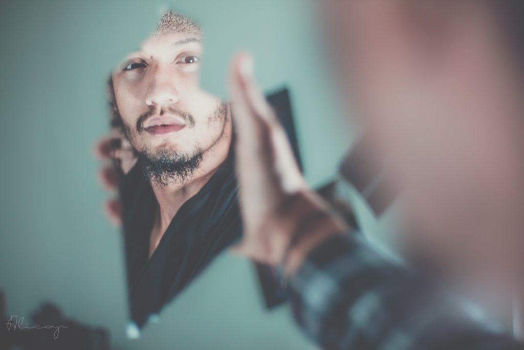 Mann sieht sein Spiegelbild