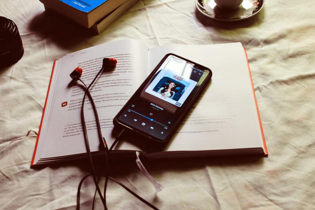 Buch und Handy und Kopfhörer liegen auf einem Tisch