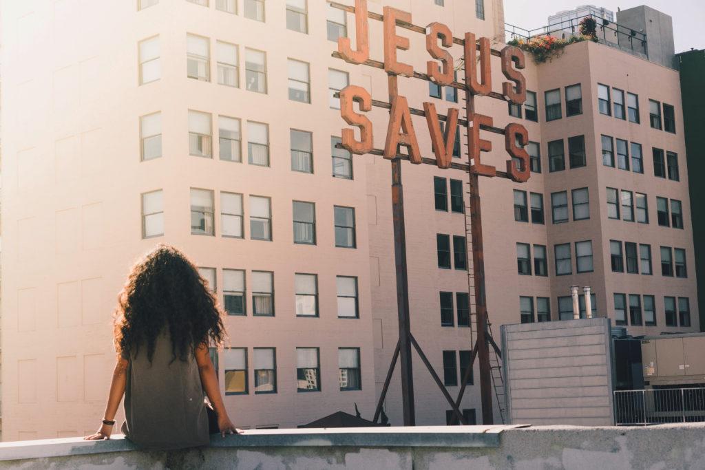 Frau sitzt auf einem Dach und schaut auf Jesus-Schriftzug