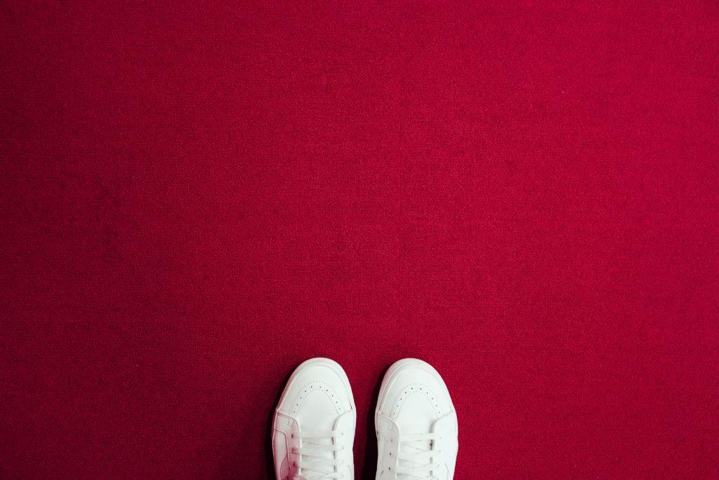 Schuhspitzen auf einem roten Teppich