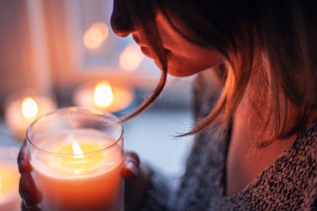 Eine Frau hält eine brennende Kerze