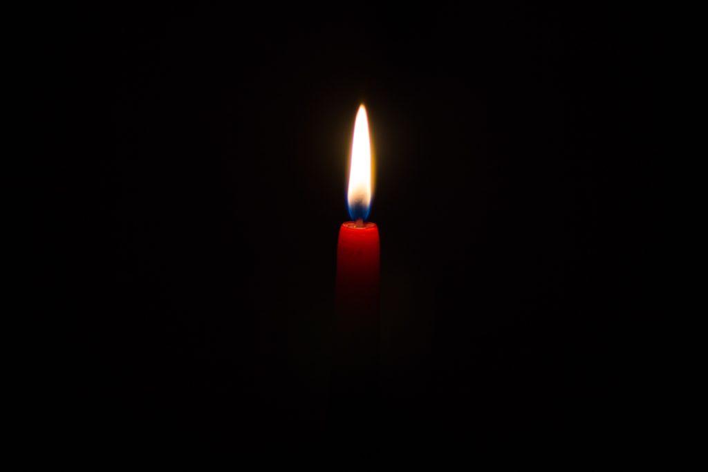 eine rote Kerze brennt in der Dunkelheit