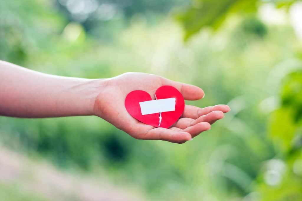 Frau hält geklebtes Herz in der Hand