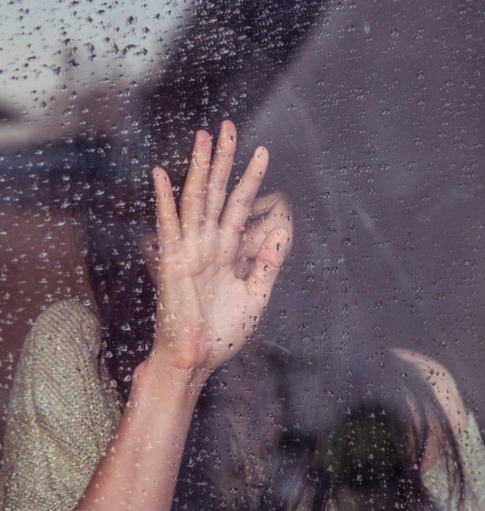 Eine traurige Frau an einer Fensterscheibe
