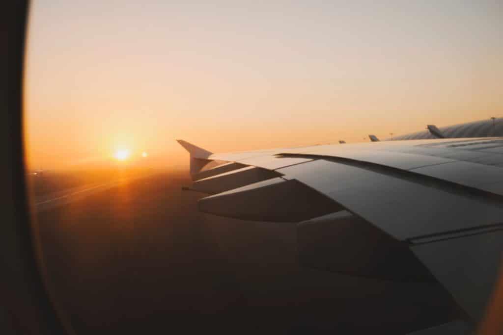 Der Flügel eines Flugzeugs mit aufgehender Sonne am Himmel