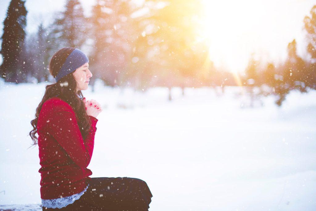 Frau sitzt im Schnee und betet