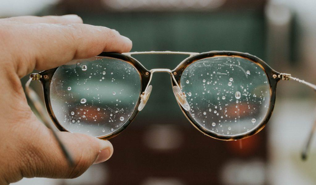 Hand, die eine Brille hält