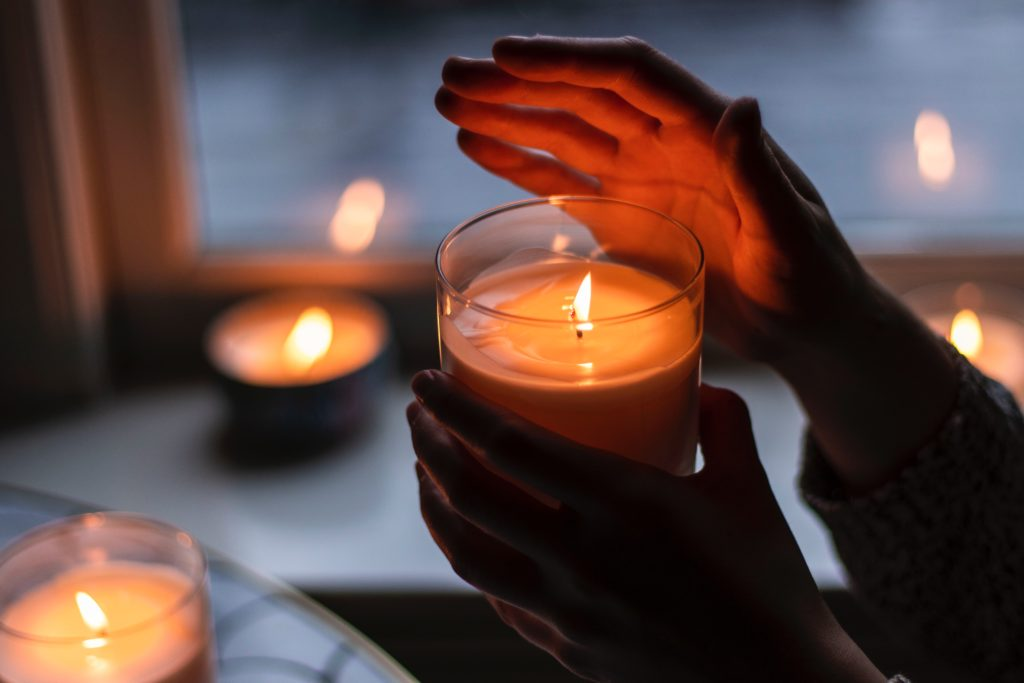 Hand hält brennede Kerze