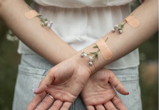 Hände mit Blumen und Pflaster