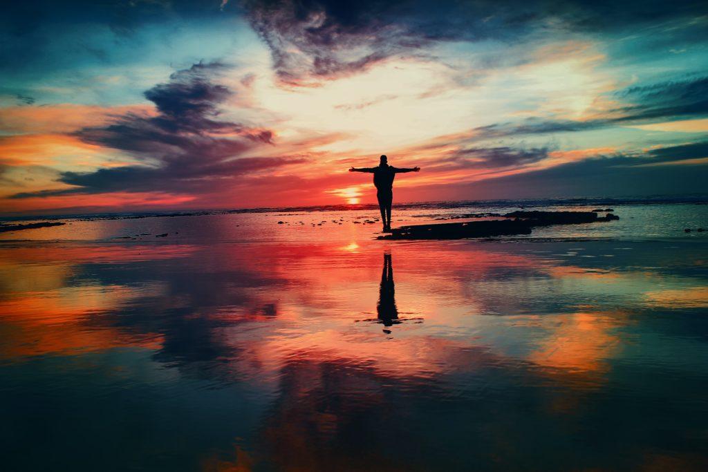 Mensch am Strand bei Sonnenaufgang