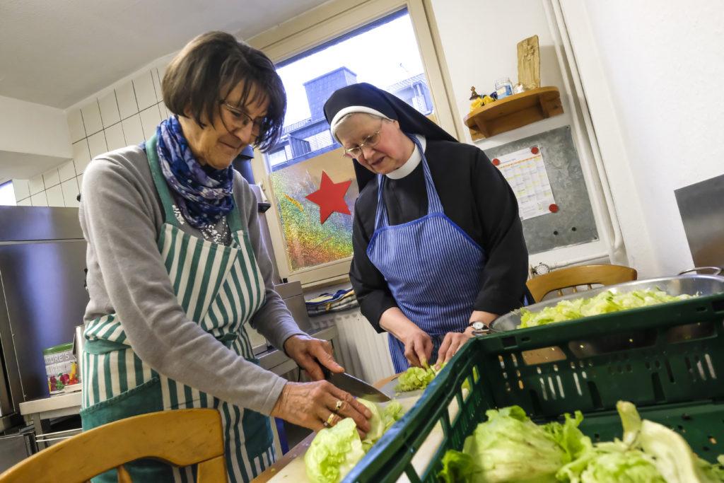 Schwester Benedicta udn eine Ehrenamtliche bereiten in der Küche der Wärmestube Essen zu.