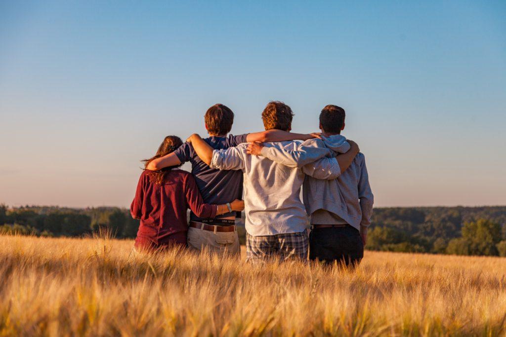 Jugendliche stehen auf einem Feld, umarmen einander