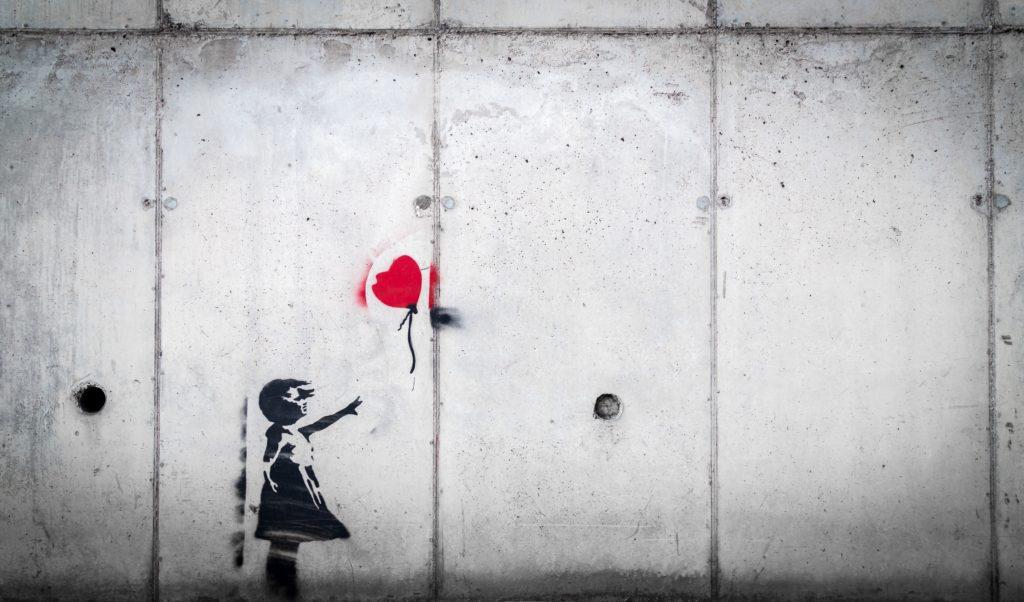 Kind mit roten Luftballon vor grauer Wand